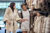 Women shopping for fur coat