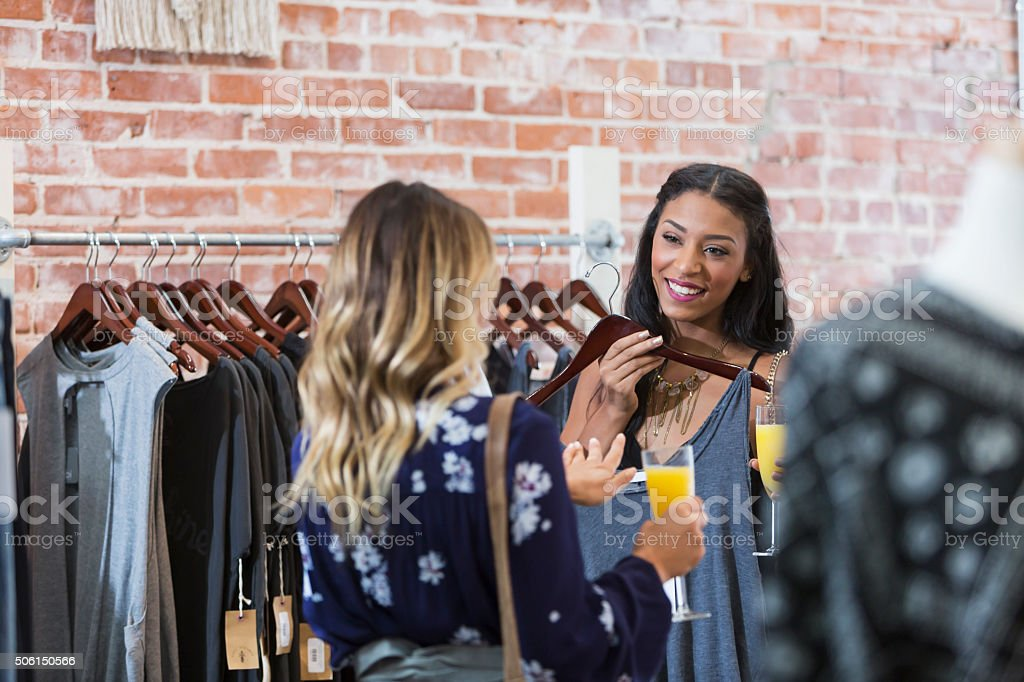 Women shopping in clothing store having drinks stock photo
