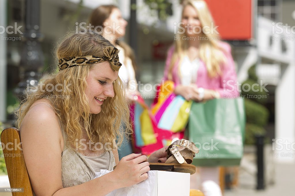 Women shopping, looking at new shoe stock photo