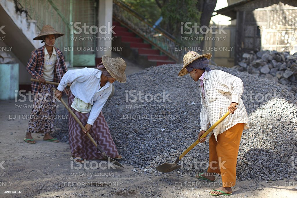 Women shoveling sand, working in road construction, Myanmar royalty-free stock photo
