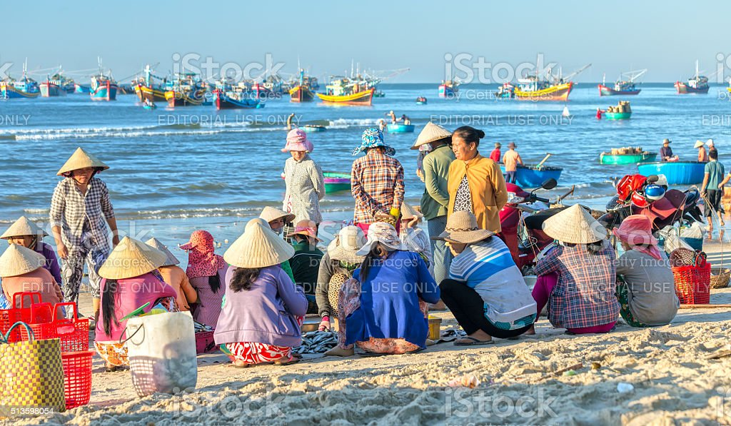 Women sit inside group fish market fishing port village stock photo