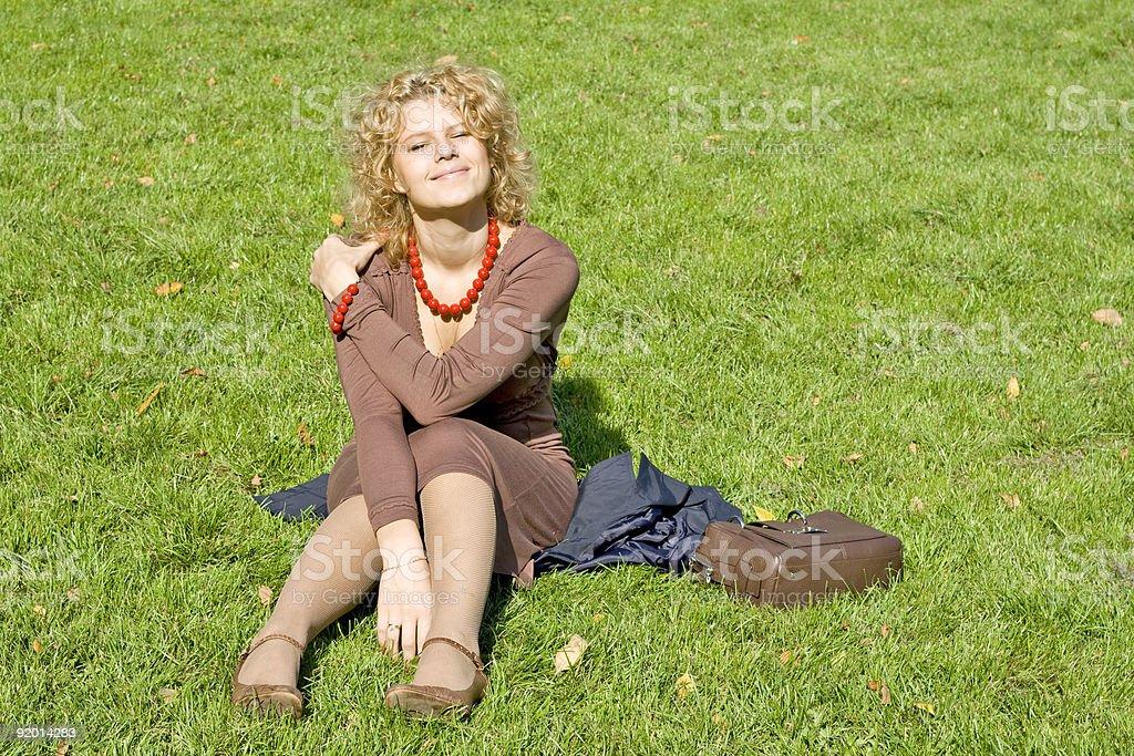 Women sits on grass stock photo