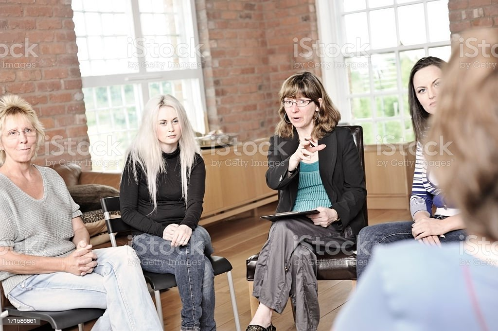 Women sitting in a circle for therapy stock photo