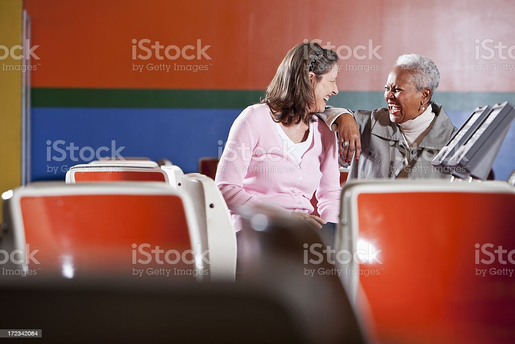 Women sitting in bowling alley stock photo