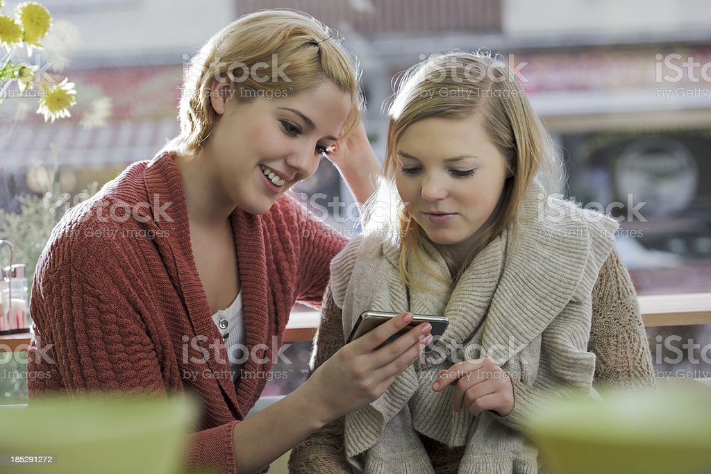 Women Sitting in Cafe with Smartphone royalty-free stock photo