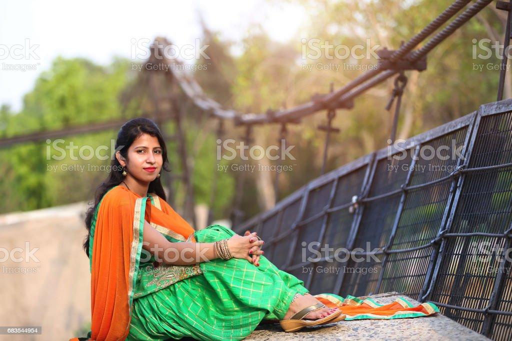 Women sitting on bridge stock photo