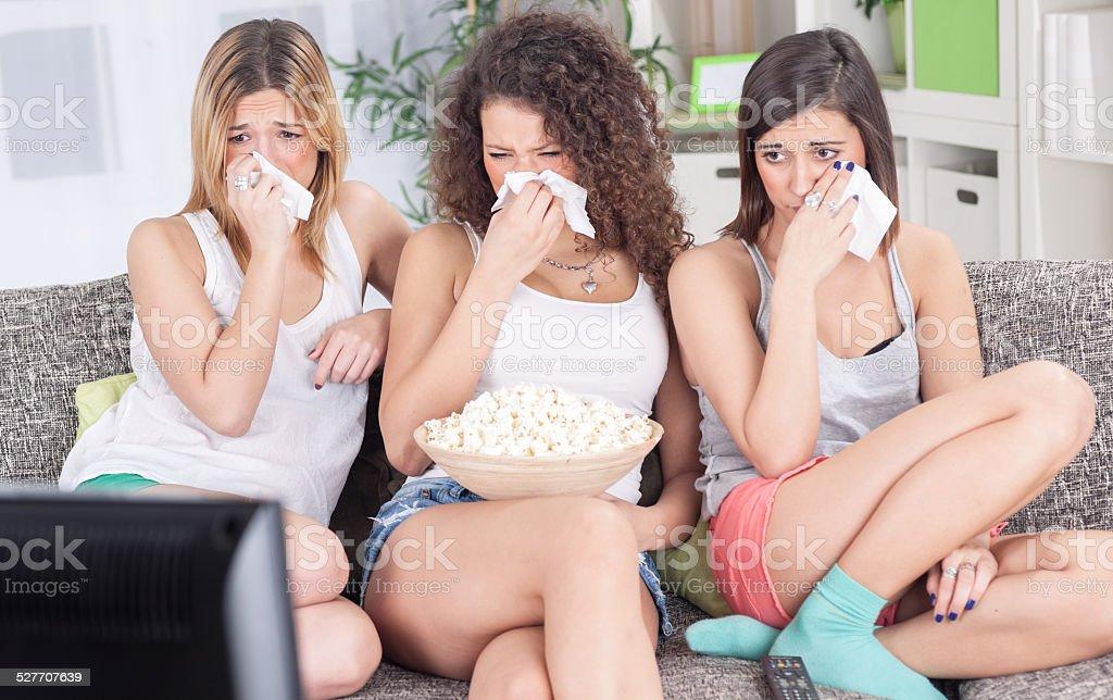 women sitting on couch watching sad movie depressed stock photo