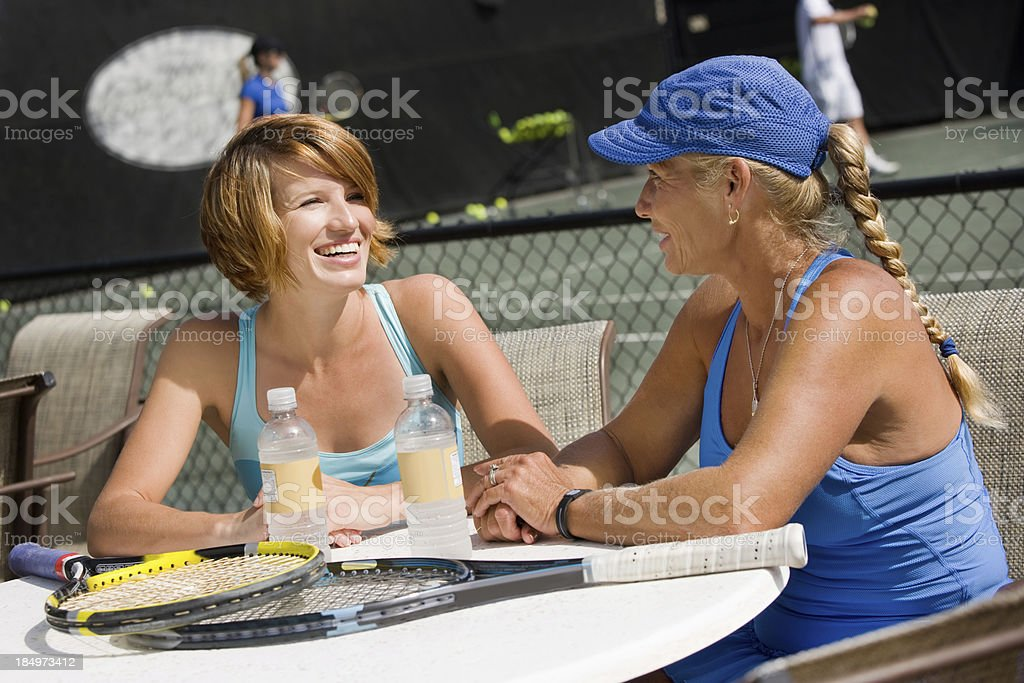 women sitting outside tennis club stock photo