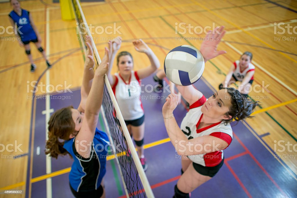 Women Spiking and Blocking a Volleyball stock photo