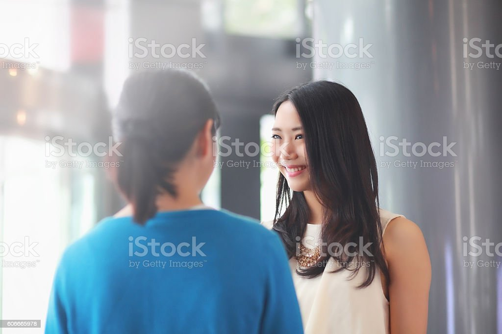 women stand talking stock photo