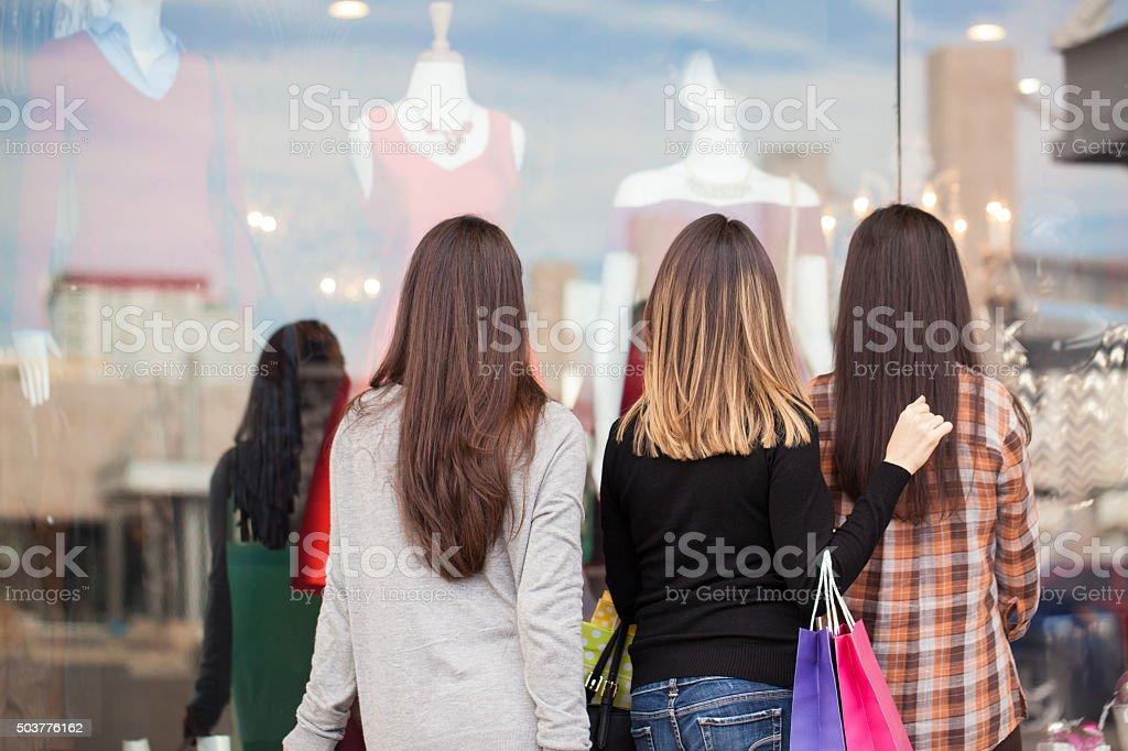 Women standing in front of a clothing store stock photo