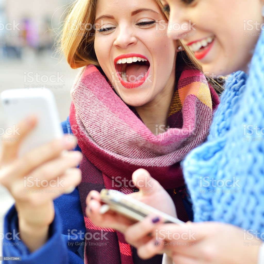 Women standing in the city and laughing on smartphone screen stock photo