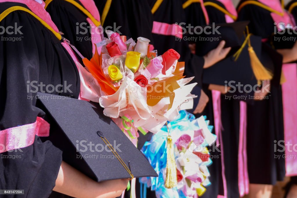 Women Student Graduate holding Flower bouquet and graduate hat in her...
