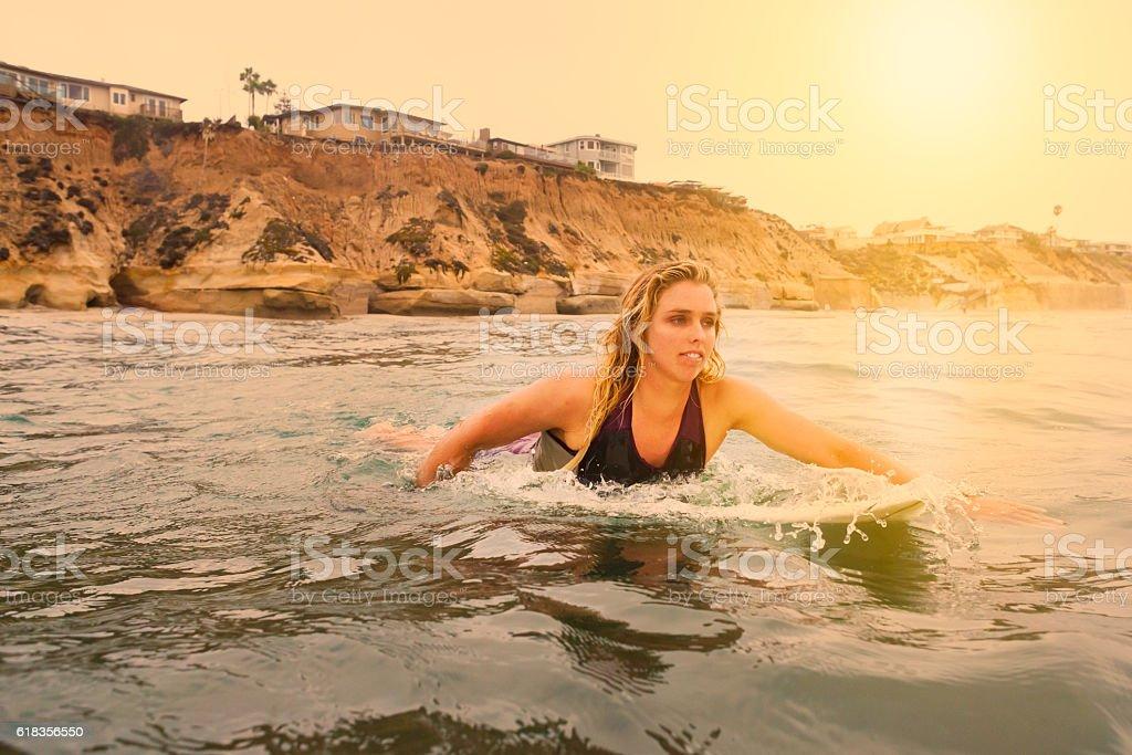 Women Surfer Paddling Into The Ocean At Sunrise stock photo