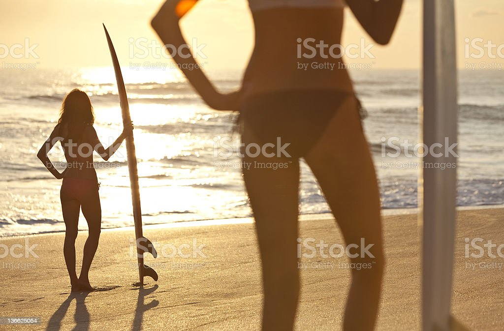 Women Surfers In Bikinis With Surfboards At Sunset Beach royalty-free stock photo