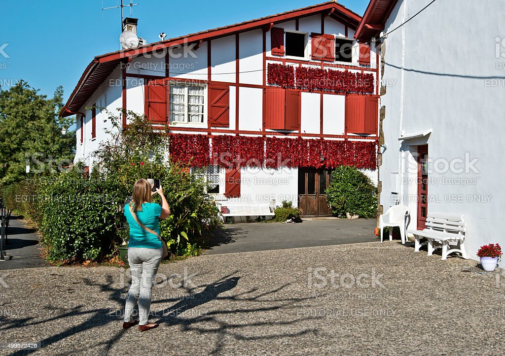 Women takes photo of peppers decorated house In Espelette stock photo