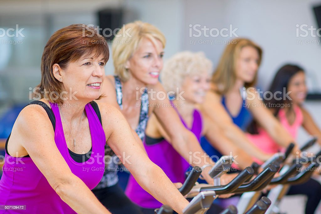 Women Taking a Cycling Class on Stationary Bikes stock photo