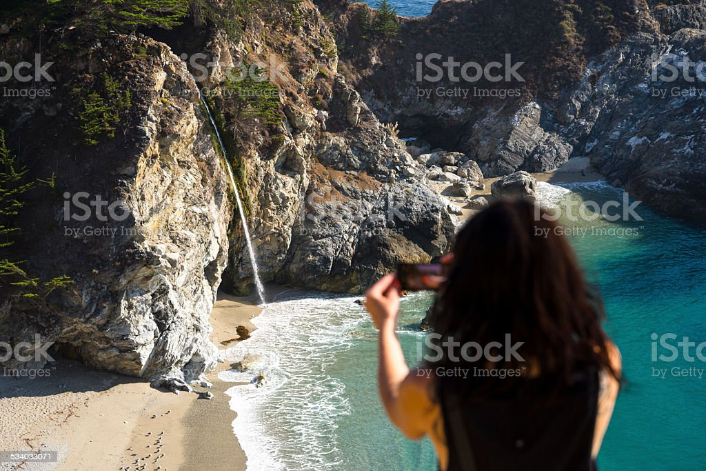 Women Taking Cell Phone Pic of McWay Falls in Focus stock photo
