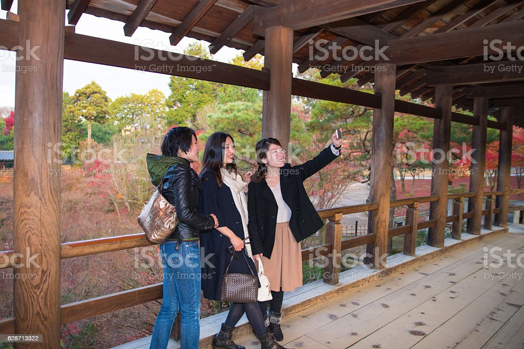 Women taking selfie pictures on wooden bridge stock photo