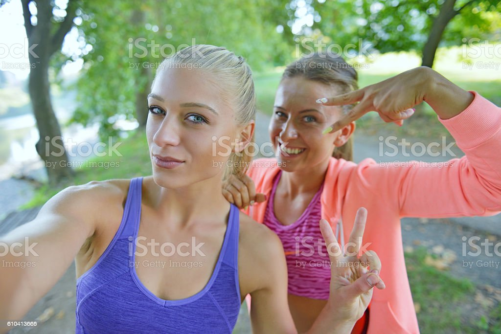 Women taking selfies after fitness exercises in the park. stock photo