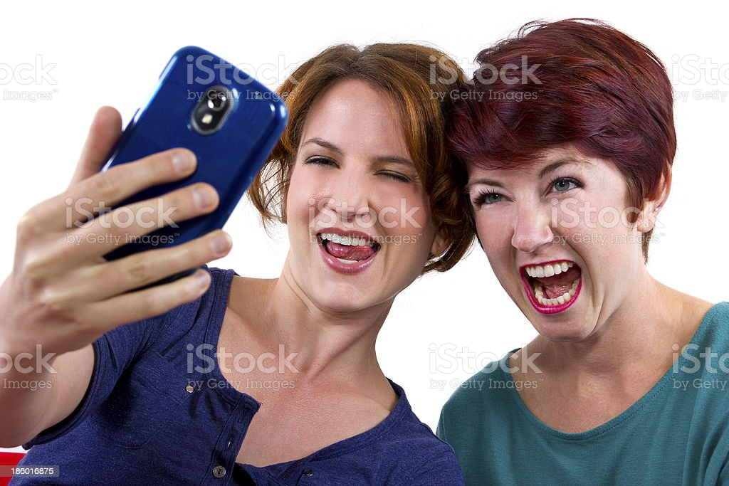 Women Taking Selfies or Self Portraits on a Cell Phone royalty-free stock photo