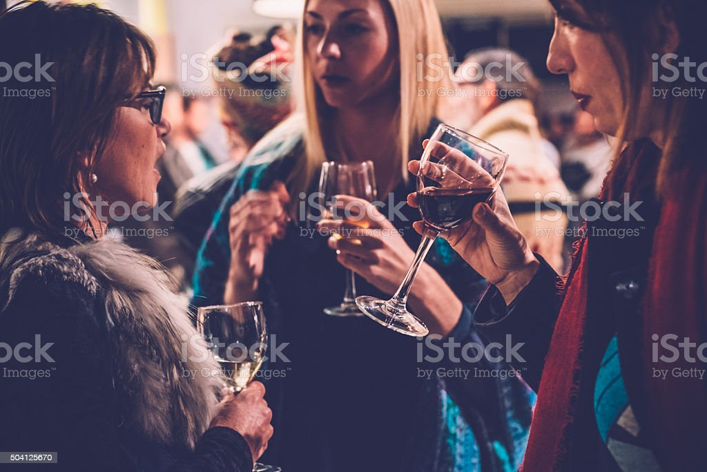 Women Talking in a Wine Bar at a Social Gathering stock photo