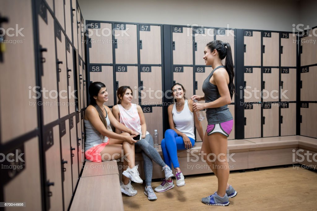 Women talking in the locker room at the gym stock photo