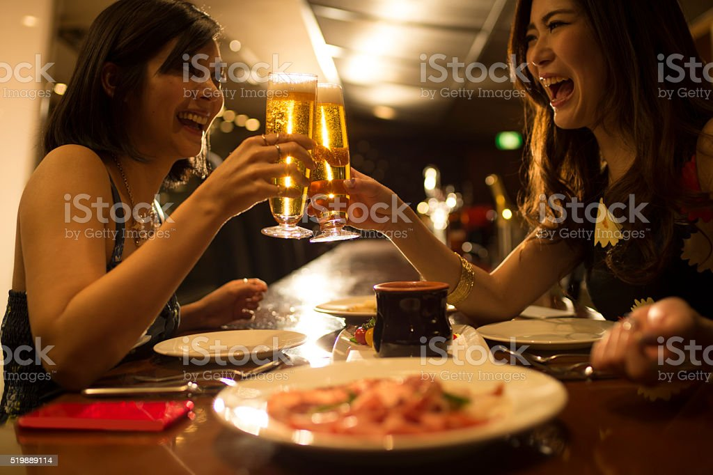 Women to toast a beer in the tavern stock photo