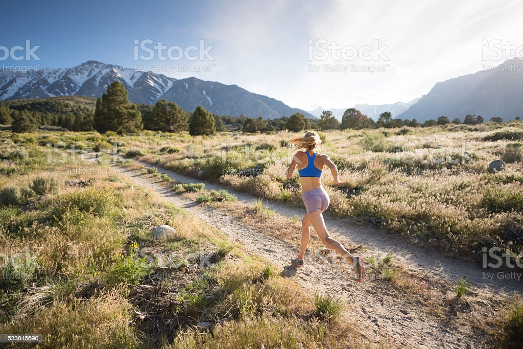 Women Trail Runner Running At Sunset In The Mountains stock photo