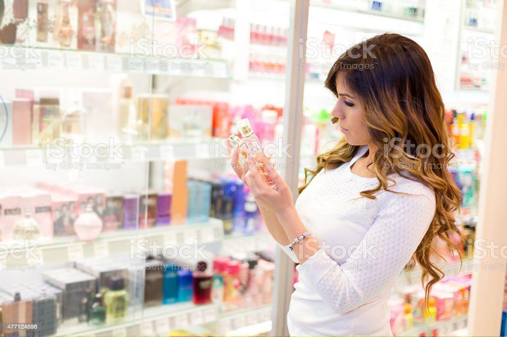 Women trying perfume in shopping mall stock photo