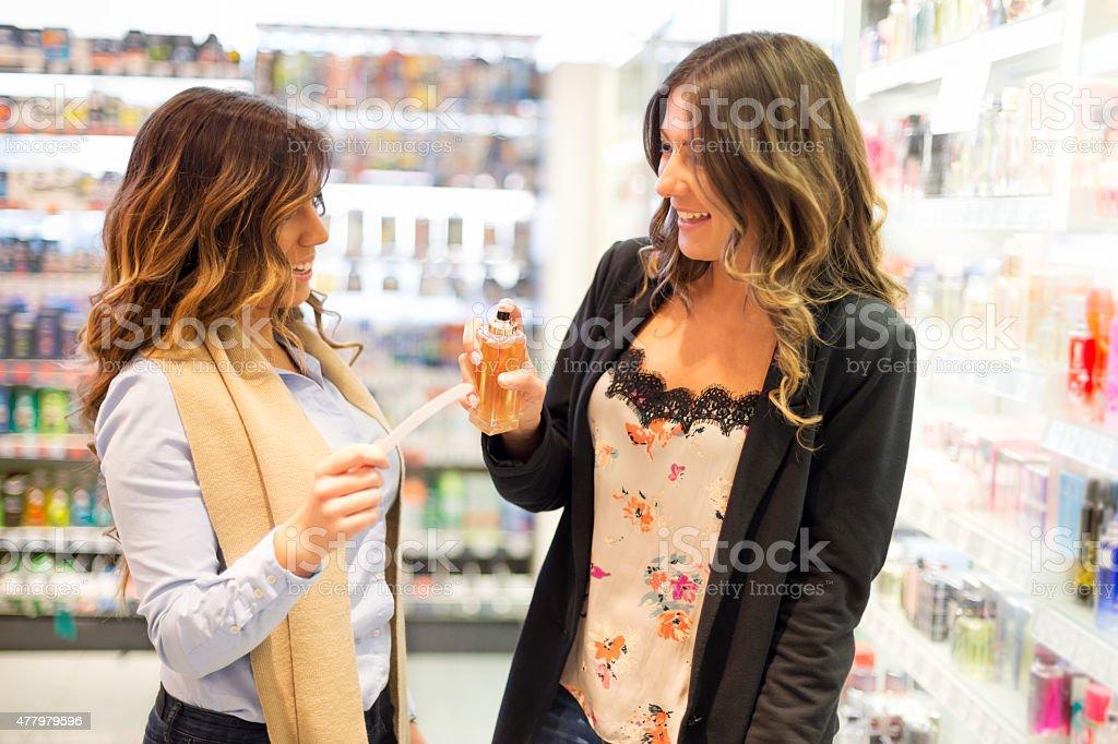 Women trying perfume in store stock photo