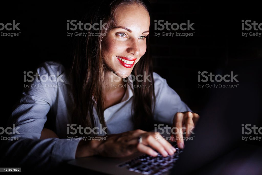 Women typing on a laptop in darkness stock photo