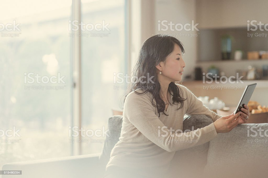 Women using digital tablet and sitting on the sofa stock photo