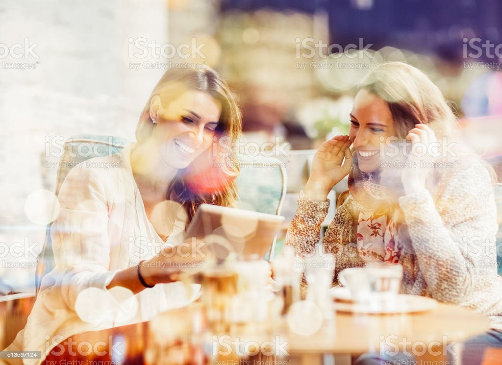 Women using tablet pc at  sidewalk cafe stock photo