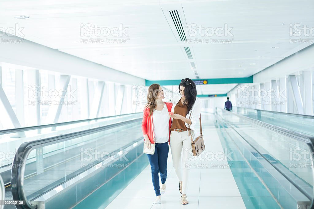 Women walking and using smart phone at airport stock photo