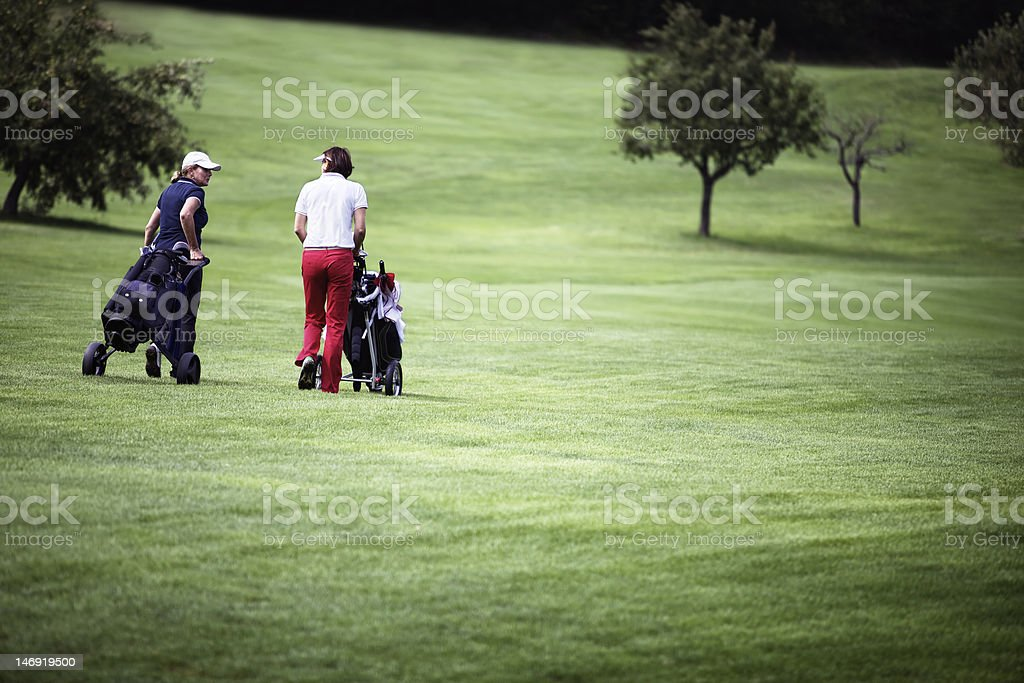 Women walking at golf course with trolleys. royalty-free stock photo