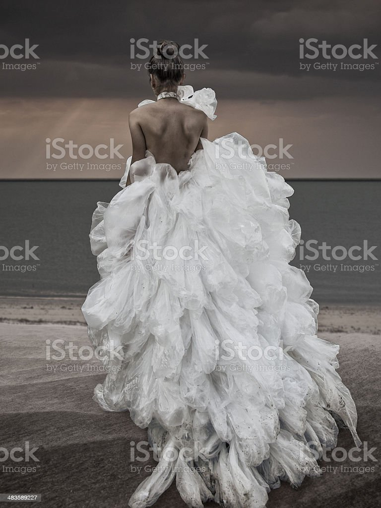women walking at the beach in plastic bag dress stock photo