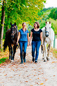 Women walking back home with horses from horseback riding