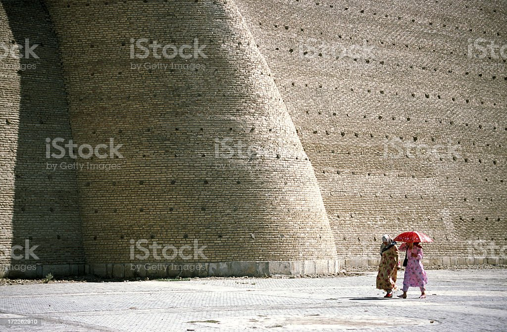 Women walking in front of a large wall, Buchara, Uzbekistan stock photo