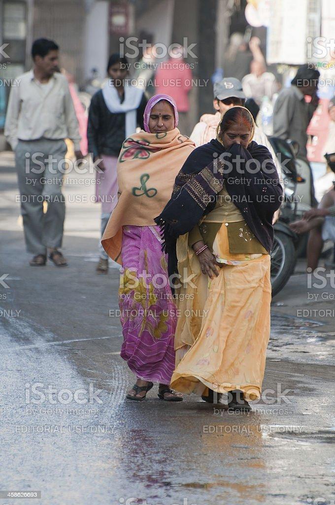 Women walking through dirty streets, Udaipur - India stock photo