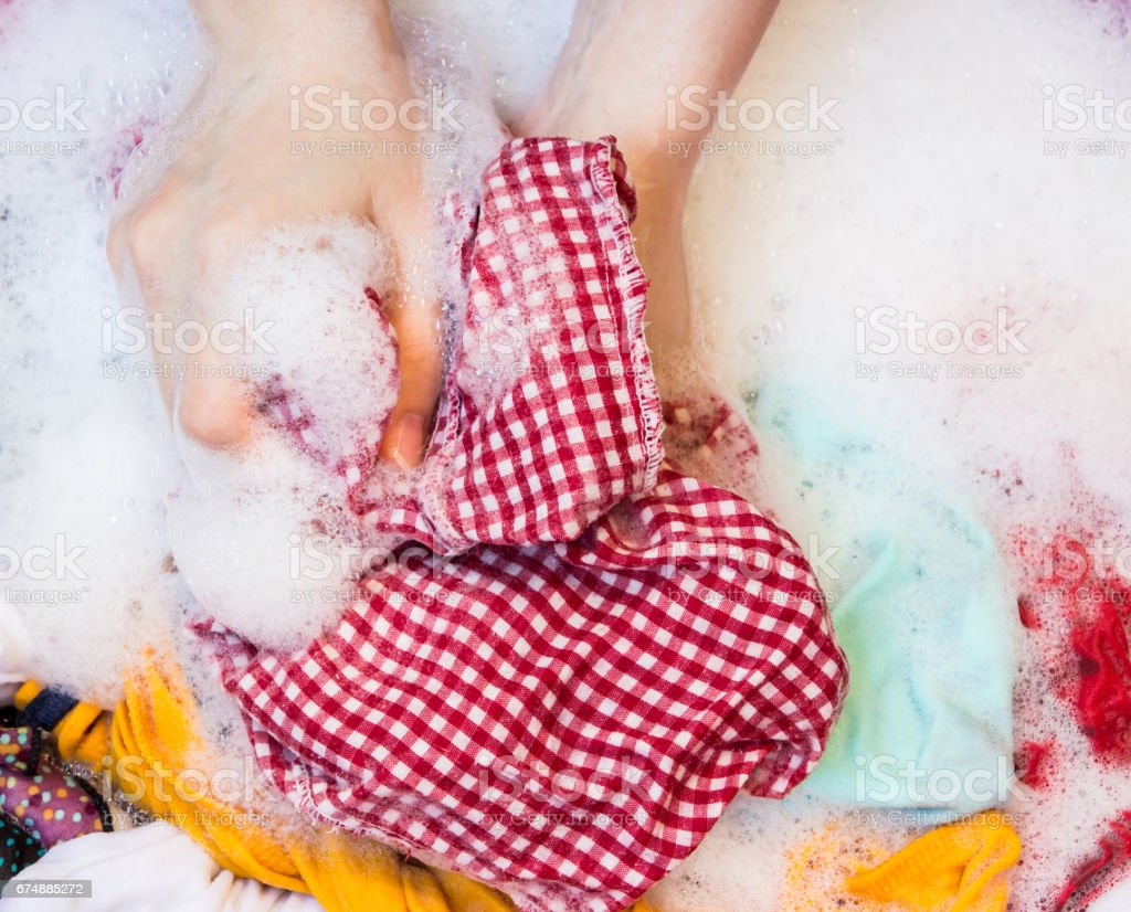 Women washing clothes in the enameled bowl stock photo