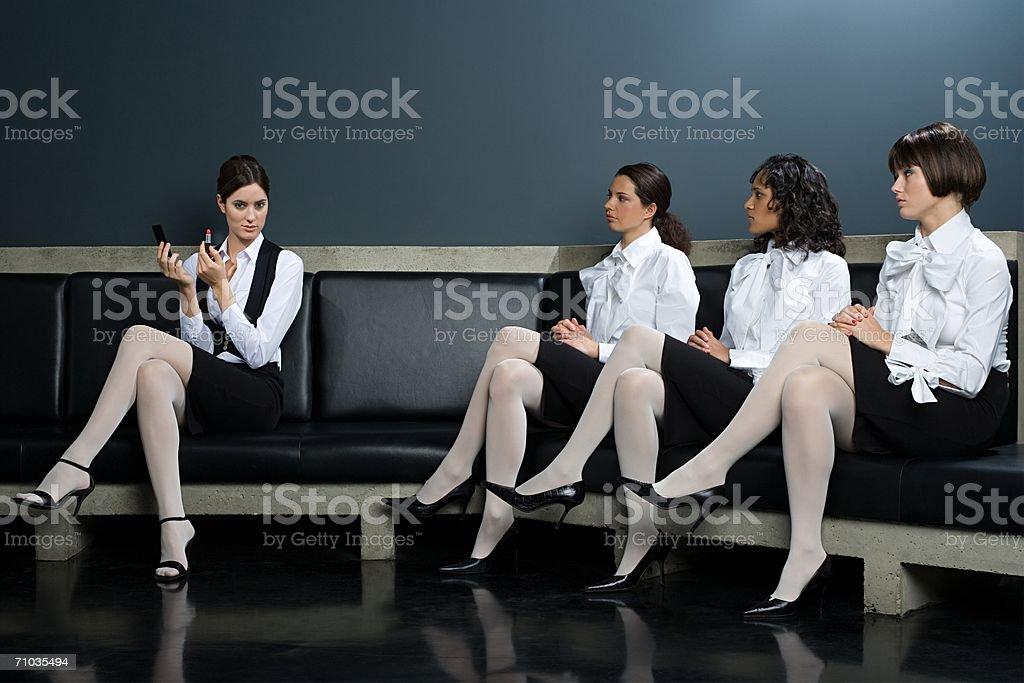 Women watching colleague apply lipstick stock photo