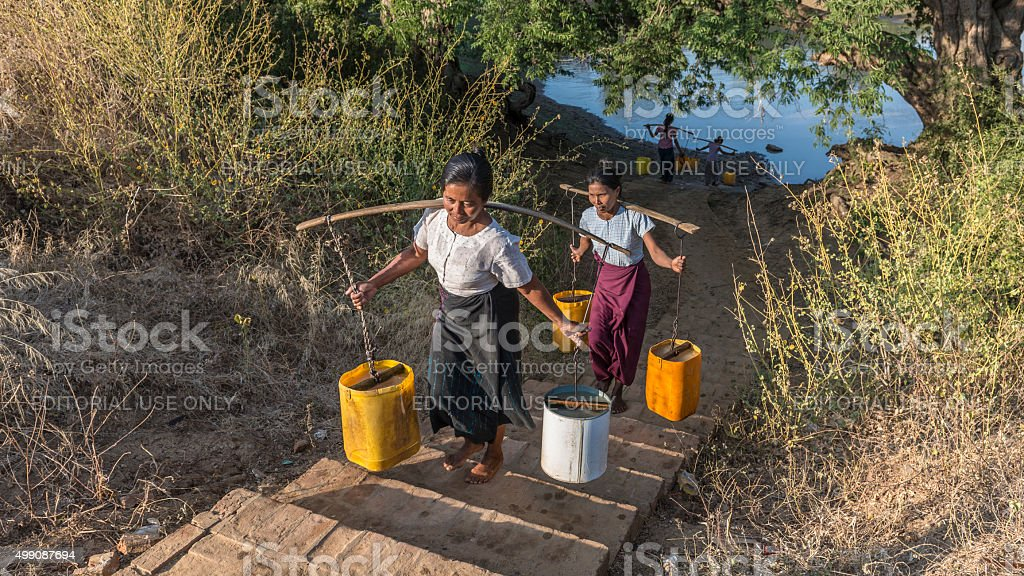 Women Water Carriers with Yoke and Buckets, Bagan, Myanmar stock photo