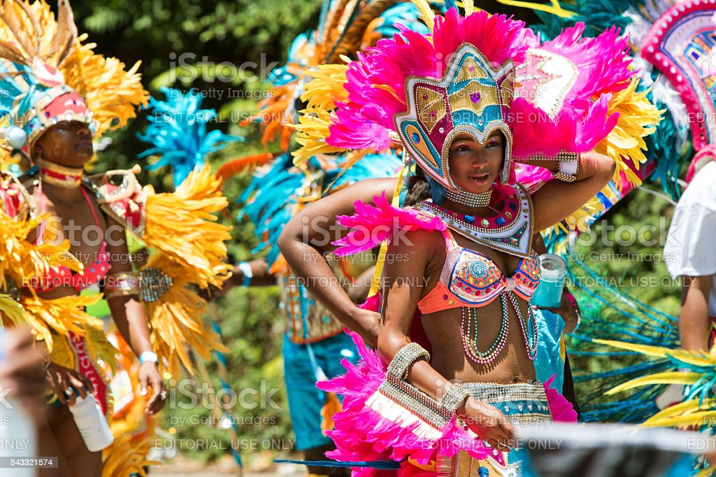 Women Wearing Costumes And Feathered Headdresses Walk In Caribbean Parade stock photo