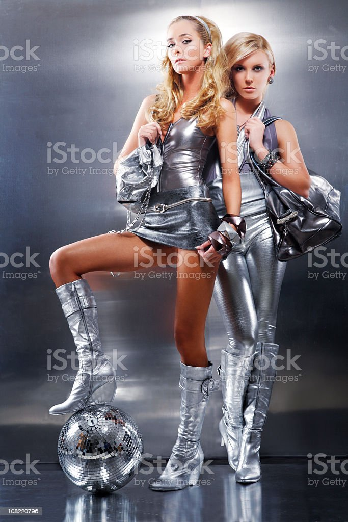 Women Wearing Futuristic Silver Clothing and Posing with Disco Ball royalty-free stock photo