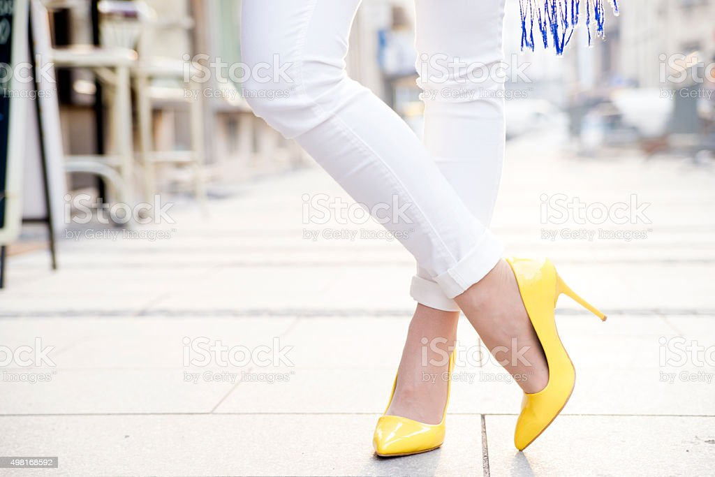 Women wearing yellow high heels in the city stock photo