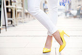 Women wearing yellow high heels in the city