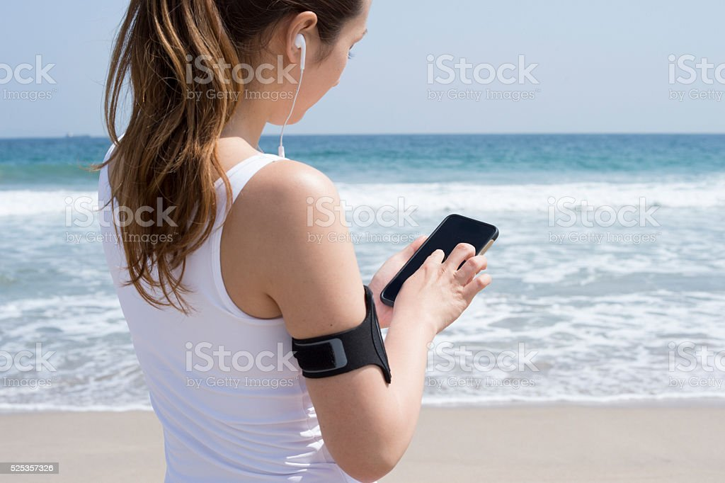 Women who are listening to music on smartphone at seaside stock photo