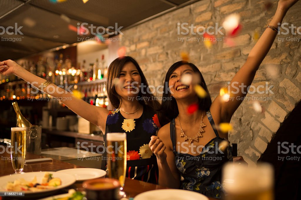 Women who are skipping the confetti at a birthday party stock photo