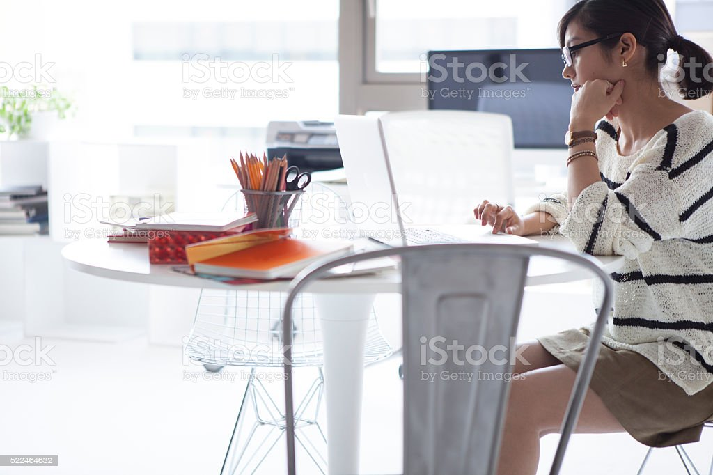 Women who are thinking about design in a laptop stock photo